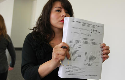 Blanca Jara, public information manager for the Circuit Court clerk's office, hands out copies of the lawsuit filed in Circuit Court today seeking a preliminary injunction to end the teachers strike.