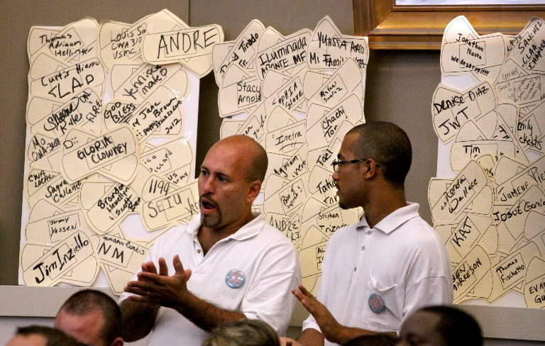 Flanked by worker signatures displayed on a poster board, referendum supporters Alex Irizarry and Stephen Irizarry (right), of Organize Now, applaud remarks as workers, businessmen, community leaders and elected officials present arguments to the Orange County Commission over a proposed referendum that would require many employers to provide sick time, during a council hearing.