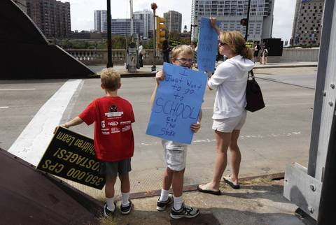 CPS students and brothers Joshua, left, and Jackson Wildermuth, join their mother Keki and a group of 18 other parents of CPS students to protest the ongoing teachers strike outside the Merchandise Mart Plaza.