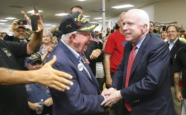 U.S. Sen. John McCain greets veteran Earle Denton of Orlando while campaigning for Mitt Romney during his stop at the Romney office in Casselberry, Florida, on September 18, 2012.