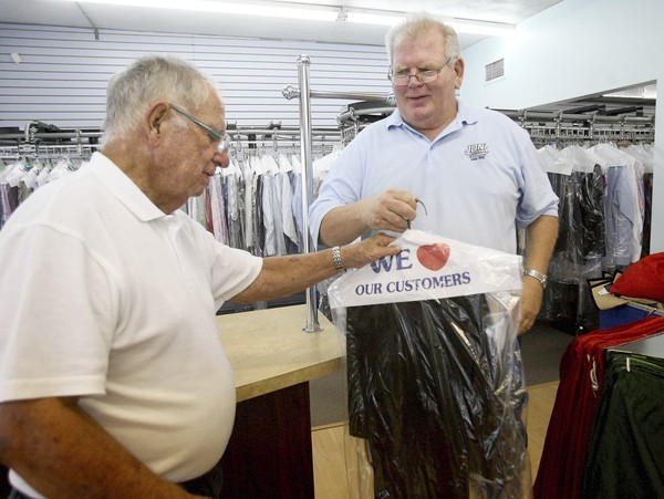 Jon Scholtens (right) is owner of Jon's Dry Cleaner and Laundry on Michigan in south Orlando. He is a third generation cleaner. He gives some clean clothes to customer Earl Downs. (George Skene/Orlando Sentinel)