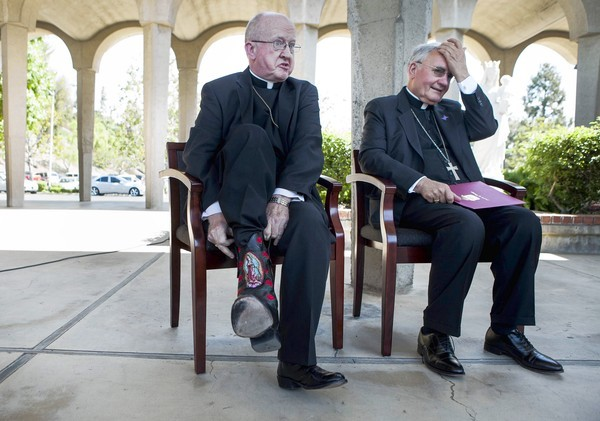 Kevin W. Vann, left, bishop of the Roman Catholic Diocese of Forth Worth, shows a boot embroidered with the image of Our Lady of Guadalupe at a ceremony announcing him as the successor to Tod Brown, right, bishop of the Diocese of Orange. Vann will assume his new duties in December.