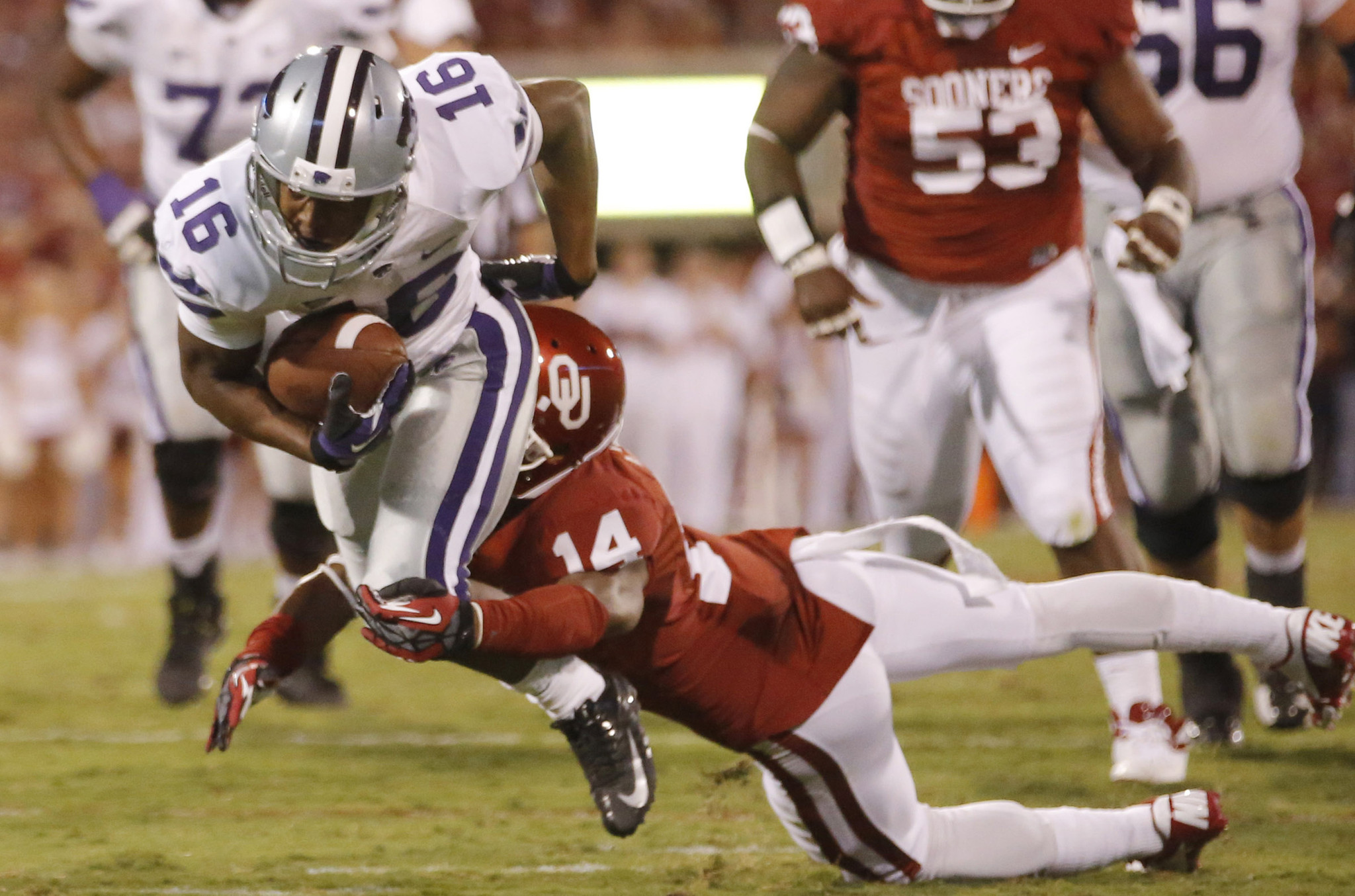 Kansas State wide receiver Tyler Lockett tries to slip away form Oklahoma defensive back Aaron Colvin.