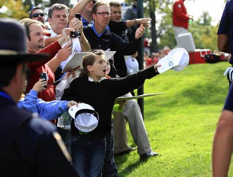 A young girl implores Tiger Woods and others to sign her hat at the second hole of the Medinah Country Club as the U.S Ryder Cup Team hits the course for practice.