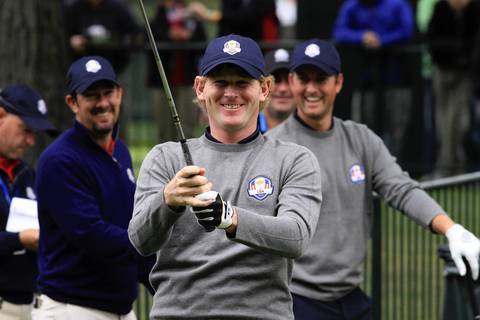 A smiling Brandt Snedeker waits to hit the ball on the practice range at Medinah Country Club before the first day of practice at the 39th Ryder Cup.