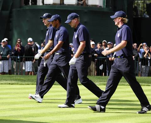 Jim Furyk, Tiger Woods, Steve Stricker and Brandt Snedeker stroll to their balls after teeing off on the first hole at Medinah Country Club.