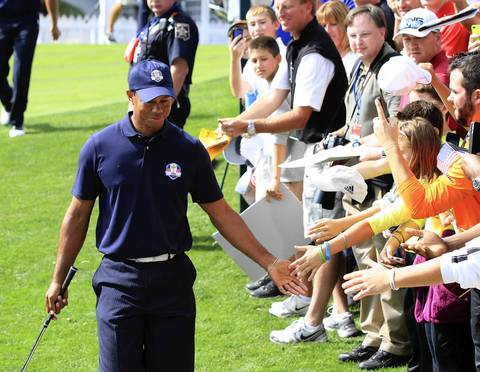 Tiger Woods low fives fans leaving the first hole at Medinah Country Club as the U.S. Ryder Cup Team hits the course today for practice.