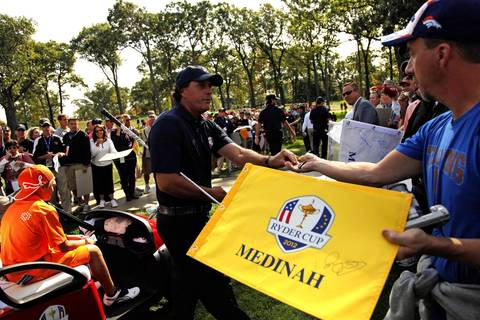 U.S. Ryder Cup team member Phil Mickelson hands off a tee to a spectator during a practice round after finishing the third hole at Medinah Country Club.