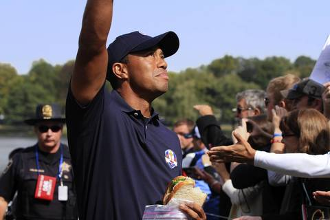 Tiger Woods tosses a souvenir into the crowd between bites of his sandwich on the second preview day of The 39th Ryder Cup at Medinah Country Golf Club.