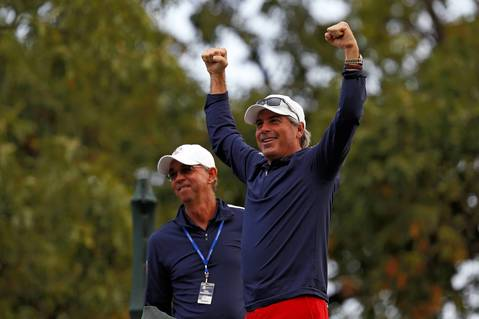 USA Ryder Cup team assistant captains Fred Couples, right, and Mike Hulbert cheer on the USA Ryder Cup team's Group 1 before they head off on the first tee during Wednesday practice at the Medinah Country Club.