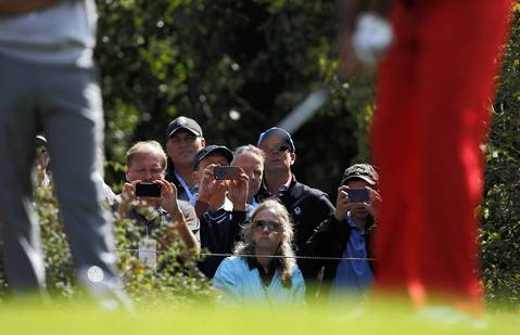 Golf fans try to get a glimpse of USA Ryder Cup team member Tiger Woods as he tees off of the tenth hole during the second day of practice at Medinah Country Club.