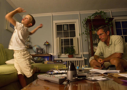 Eight-year-old Bradley Garner lets off steam during a game of Griddly Headz Baseball with his father, Jim, at home.