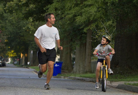Jim Garner runs alongside of his eight-year-old son, Bradley, in their neighborhood in mid-August.