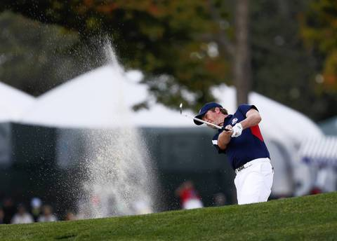 USA Ryder Cup Team member Webb Simpson hits out of the sand on the first fairway during Thursday's practice round at Medinah Country Club.