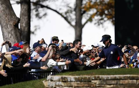 USA Ryder Cup Team member Bubba Watson has some fun giving low fives to spectators after his group tees off on the first hole at Medinah Country Club on Thursday.
