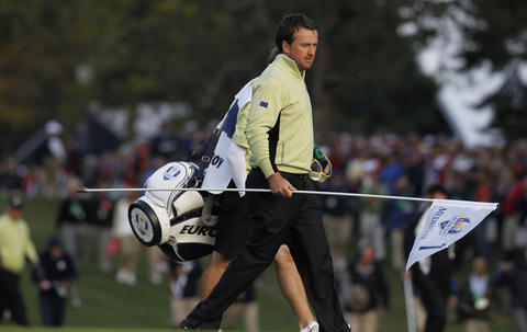 Graeme McDowell of the Europe Ryder Cup teams moves the flag on the first hole at Medinah Country Club as competition begins in the 2012 Ryder Cup.