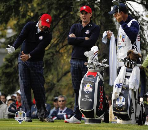 USA Ryder Cup Team member Phil Mickelson, left, goes over his shot with teammate Keegan Bradley on the fourth tee on the first day of competition at the 2012 Ryder Cup.