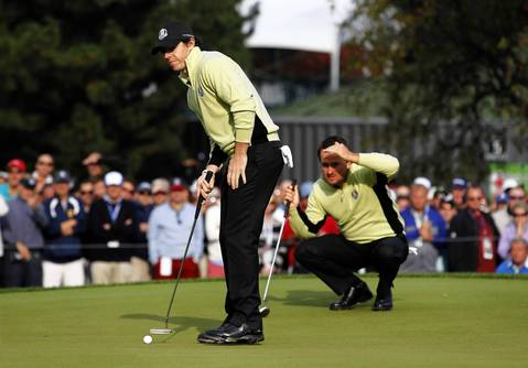 European Ryder Cup Team member Rory McIlroy lines up a shot with teammate Graeme McDowell on the eighth tee on the first day of competition at the 2012 Ryder Cup.
