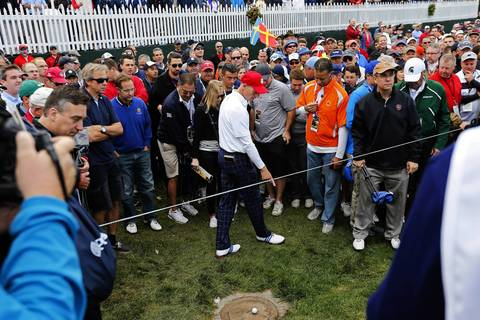USA Ryder Cup Team member Jim Furyk finds his ball behind the spectator rope on the eighth fairway on the first day of competition at the 2012 Ryder Cup.