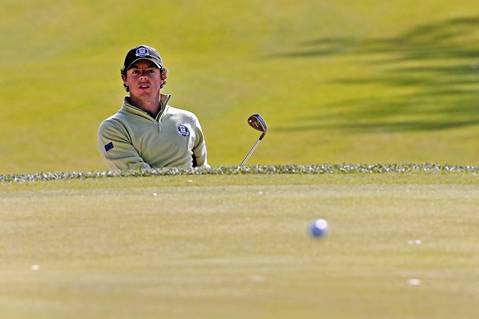 European Ryder Cup Team member Rory McIlroy hits the ball out of the sand on the tenth fairway on the first day of competition at Medinah Country Club.