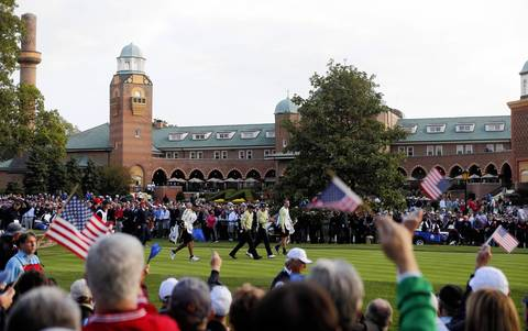 Fans wave thier flags as players walk the first hole during the first round of the Ryder Cup at Medinah Country Club