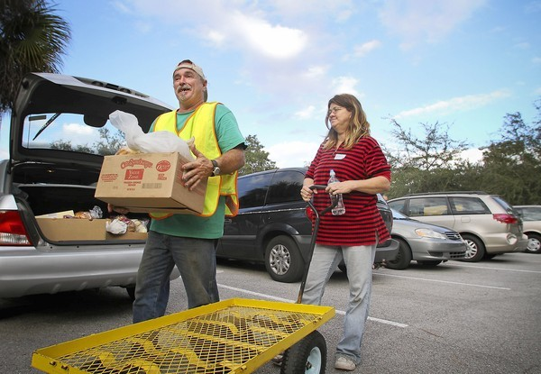 David Rugg and his wife, Alda, help carry food to people's cars at Tuskawilla United Methodist Church in Casselberry.