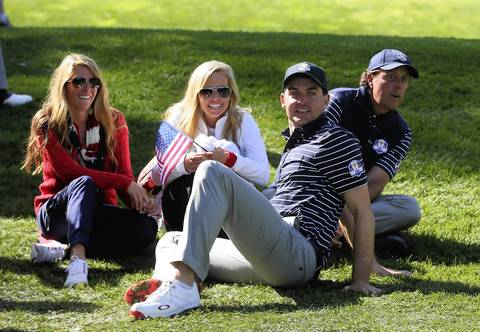 USA's Keegan Bradley and Phil Mickelson, right, watch teammates Jimm Furyk and Brandt Snedeker during the morning foursomes. Bradley's girlfriend Jillian Stacey is at left with Mickelson's wife Amy.