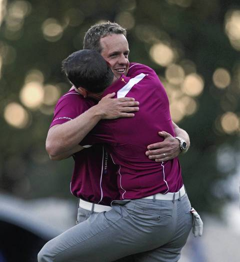 Team Europe's Luke Donald, facing, gets a hug from teammate Sergio Garcia after their match win. Donald birdied three of the last five holes in four-balls as he and Sergio Garcia held off Tiger Woods and Steve Stricker.