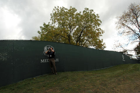 A police officer scans the crowd entering Medinah Country Club for final day of Ryder Cup in Medinah on Sunday, Sept. 30, 2012.