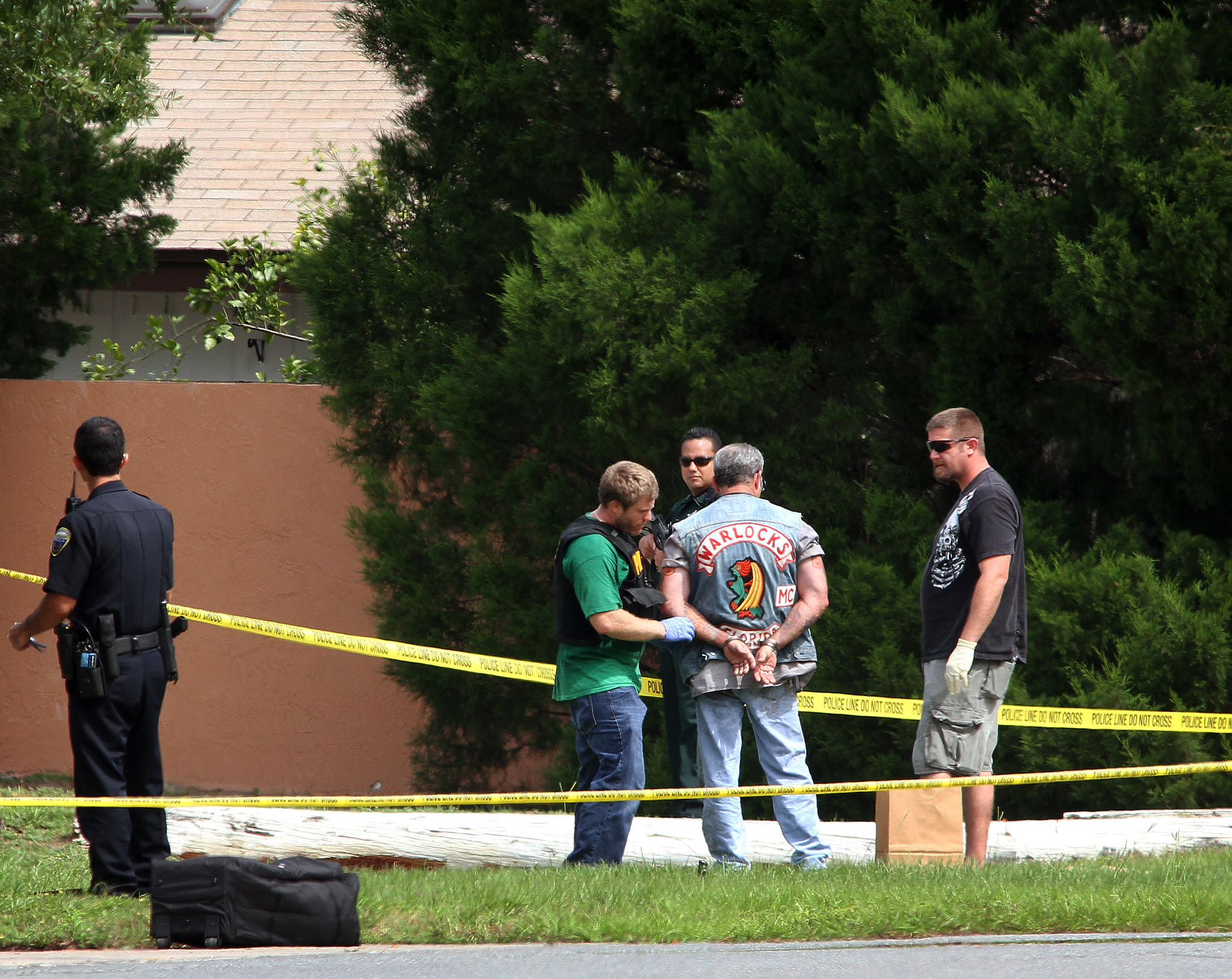 Law enforcement members talk to a man with a Warlocks logo on his jacket at the VFW in Winter Springs on September 30, 2012. A shooting this morning at VFW Post 5405 in Winter Springs has left two people dead and one critically injured, according to police. Several men could be seen in handcuffs as the scene was being investigated.