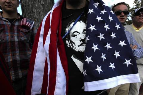 A fan wears an American flag draped over his Bill Murray t-shirt along the 4th fairway.