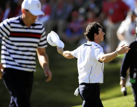 Europe's Rory McIlroy celebrates his win as the United States' Keegan Bradley walks off the 17th green.