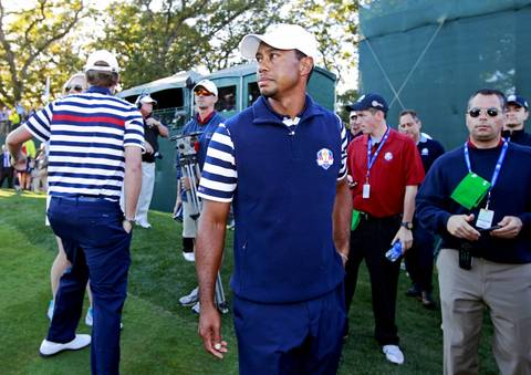 Tiger Woods takes one last look at the opposing team celebrations before heading out of the 18th green.