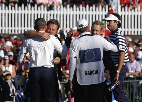 Bubba Watson walks away as Europe's Sergio Garcia gets a hug from Graeme McDowell on the 18th hole.