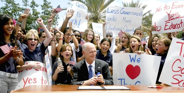 Gov. Rick Scott smiles as charter school students cheer after he signed the state budget during an outdoor ceremony in The Villages on Thursday, May 26, 2011.