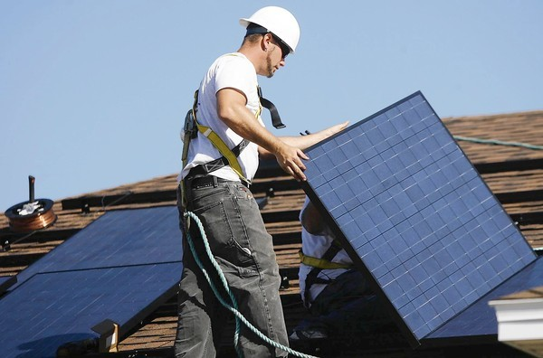 Troy Simmons, with Blue Chip Energy of Lake Mary, installs solar panels on the roof of a model home for KB Homes on Mountain Apple Way in Apopka on Thursday, January 19, 2012. KB Homes is adding solar panels as a standard feature on new homes. (Stephen M. Dowell/Orlando Sentinel)