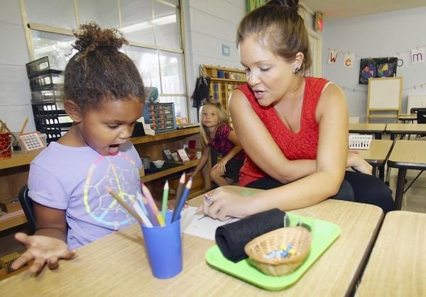Teacher Danielle Penn works with Ava Thomas.