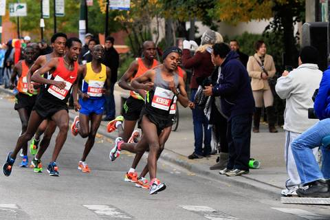 Tsegaye Kebede, of Ethiopia, center takes the lead while Tilahun Regassa, of Ethiopia, left, follows in Chicago's Pilsen neighborhood during the Bank of America Chicago Marathon.