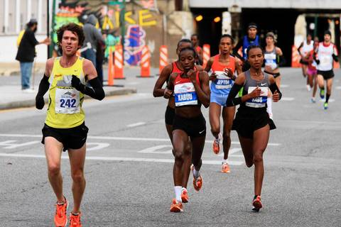 Lucy Kabuu, of Kenya, left center, and Fatuma Sado, of Ethiopia, right center, are neck-and-neck as they head through Chicago's Pilsen neighborhood during the Bank of America Chicago Marathon.