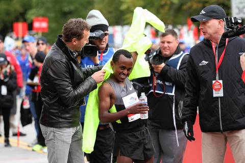 Tsegaye Kebede gets help with his jacket after becoming the first Ethiopian to win the Bank of America Chicago Marathon, breaking the year-old course record by nearly a minute.