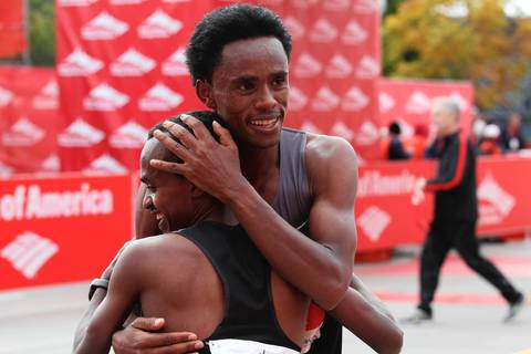 Tsegaye Kebede, front, becomes the first Ethiopian to win the Bank of America Chicago Marathon, breaking the year-old course record by nearly a minute.