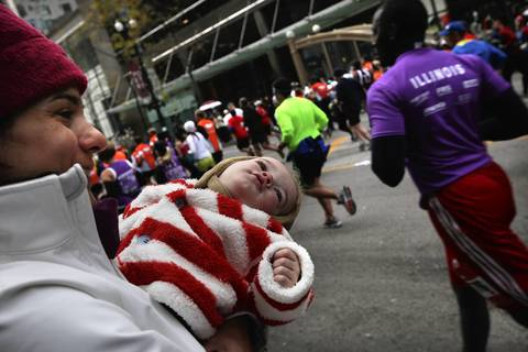 Pamela Huber, of Boston, with her one-year old son Trevor, 1, watches for her husband to run down State Street during the Bank of America Chicago Marathon.