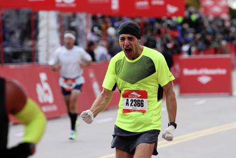 A runner celebrates crossing the finish line at the Bank of America Chicago Marathon.