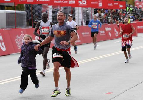 A runner crosses the finish line on Columbus Drive with a young helper at the Bank of America Chicago Marathon.