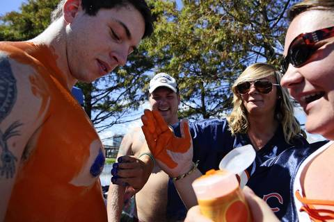 Jake Sesemann, of St. Augustine, Fla., left, has orange and blue body paint pasted on by Ryan Cortez of Chicago, right, and Nicole Lesage, second from right, while tailgating outside EverBank Field in Jacksonville, Florida.