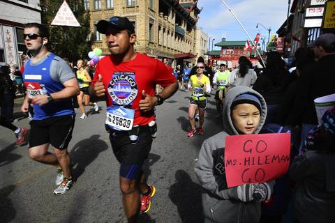 Brendon Xu, 8, has his photo taken by his mother as he waits for his teacher assistant at Skinner school to pass by in Chinatown during the 35th Chicago Marathon.