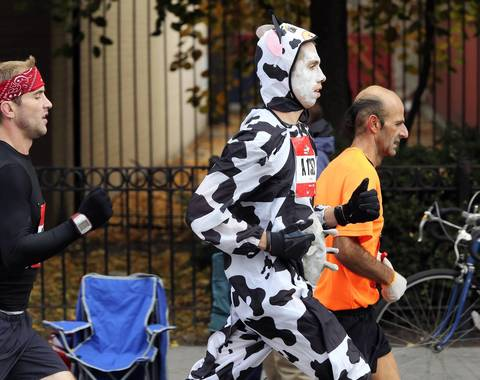 The streets of the Pilsen neighborhood are filled with runners, including one disguised as a Holstein, at mile 19 of the Bank of America Chicago Marathon.