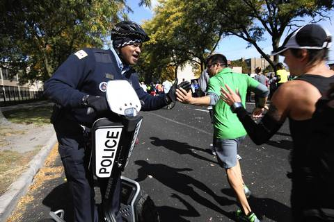 Chicago police officer Craig Williams encourages runners at the turn from 35th Street onto Michigan Avenue as they head towards the home stretch of the 35th Bank of America Chicago Marathon.