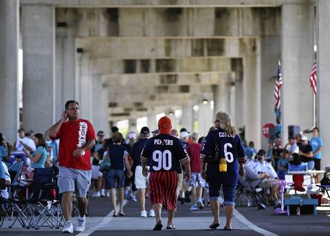 People walk through a highway underpass while tailgating outside EverBank Field.