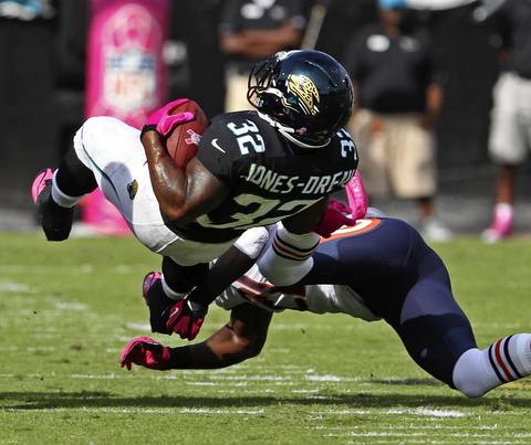 Jaguars running back Maurice Jones-Drew is tackled by Major Wright during the first quarter.